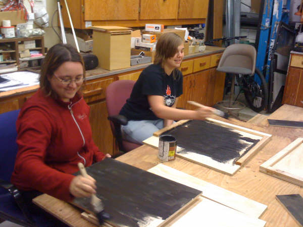Angela Ross and Jennifer Dunn applying stain to the bat houses.