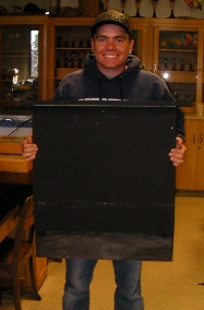 Jordan Mackey holding one of the finished bat houses.